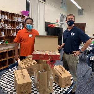 2 men standing in school with donated breakfast