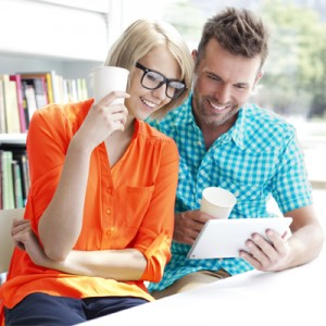 Couple in library working with digital tablet