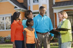 family looking at a home with a real estate agent
