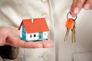 person holding a small house in one hand and keys in the other hand