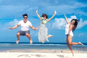 three people on the beach jumping in the air for a photo