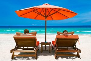 couple sitting in two lounge chairs under an umbrella at the beach