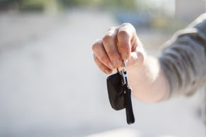 man's arm holding car keys out
