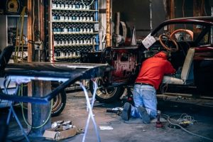 man working on a car in a repair shop