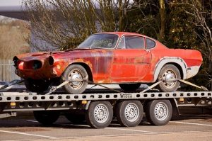 old red mustang being towed away on a tow truck