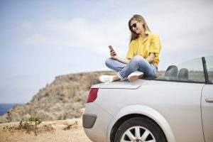 girl sitting on top of a car texting on her phone