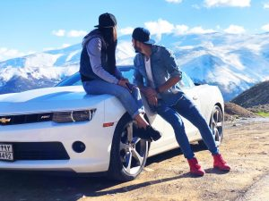 young couple sitting by a sports car looking at a mountain
