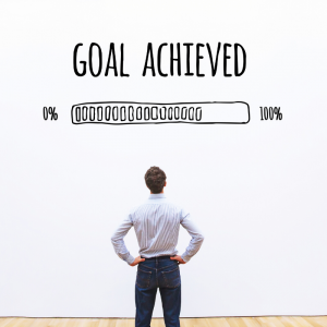 "Man standing in front of a wall with ""Goal Achieved"" written on the wall. Avoid Holiday Impulse Shopping"