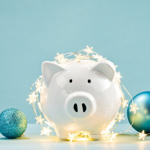 A white piggy bank sitting in front of blue background covered with holiday lights and ornaments. Overcome Holiday Impulse Purchases