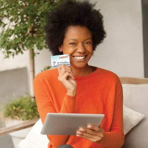 Woman in orange shirt holding an ipad and a credit card