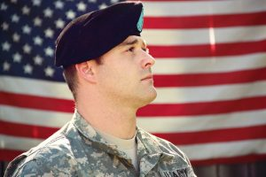 U.S. soldier in front of a United States flag