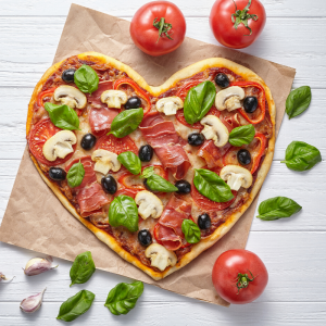 Heart shaped pizza surrounded by tomatoes and basil