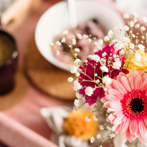 a breakfast tray with coffee, cereal, and a bouqet of pink flowers.