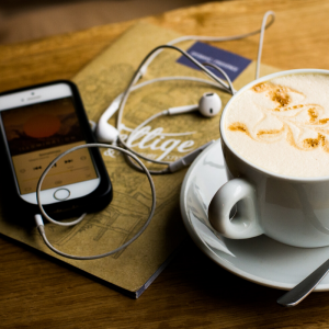 an iphone with headphones and a cup of coffee