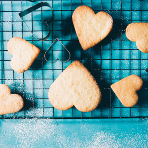 a tray of heart shaped sugar cookies on a blue countertop