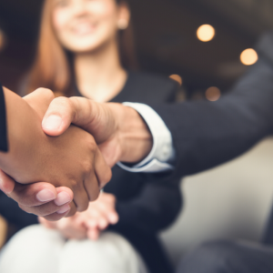 a man and woman shaking hands completing a job interview.