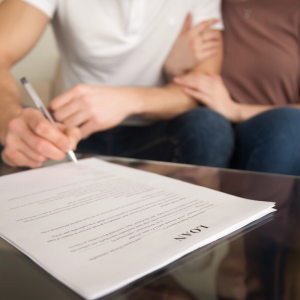 Two people signing a loan document.