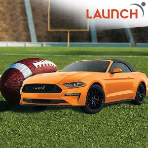 Orange Car and football sitting on a football field