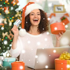 Woman with a gift card in one hand and a present in the other wearing a Santa hat shopping online