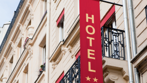 Exterior of a hotel with a red banner.Avoid Holiday Travel Stress