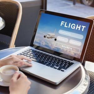 A woman typing on the laptop looking for airline flights