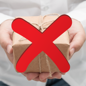 A woman in a white shirt holding a small present wrapped in brown paper with a large red X over the package. Avoid Holiday Travel Stress