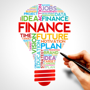 A light bulb filled with financial words, goals, finance, idea, data. A hand with a pen is below. Jump Start 2020 Financial Resolutions