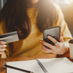 A woman with brown hair and yellow turtle neck holding a credit card and phone. Jump Start 2020 Financial Resolutions