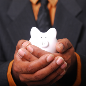 A man in a suite with orange shirt holding a piggy bank. Jump Start 2020 Financial Resolutions