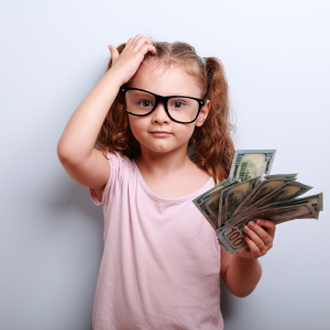 A girl with pigtails wearing a pink shirt scratching her head holding money