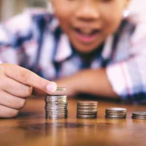 A kid in a plaid shirt counting coins