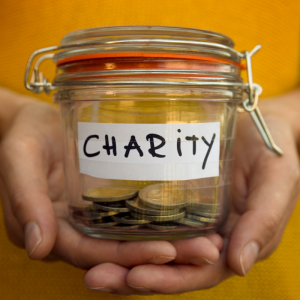 Someone holding a jar filled with coins labeled | Charity
