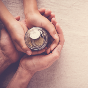 Parent holding child's hands holding a jar full of money