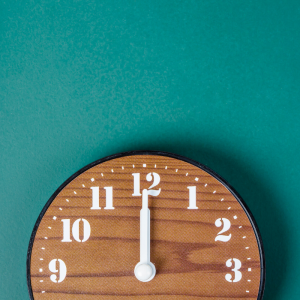 a wood clock laying on a teal background