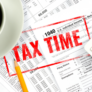 A coffee cup sitting on a pile of tax documents | Tax Time