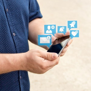 A man wearing blue shirt holding cell phone with social media icon bubbles sprouting from it