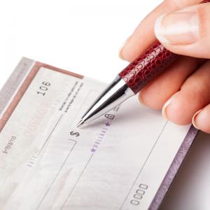 Closeup of a hand writing a check