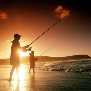 Two men fishing on the beach at sunset