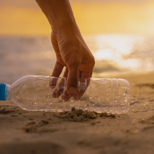 A hand picking up an empty plastic bottle on the beach at sunset