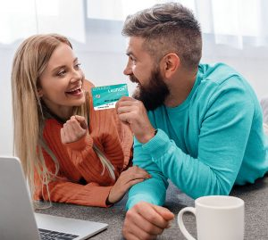 Couple holding the Rewards Card in front of a laptop