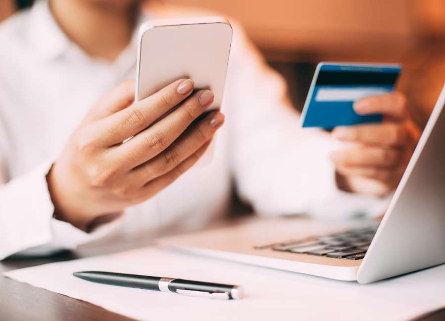 Woman holding credit card and phone