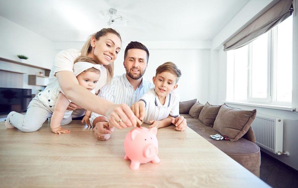 Family putting money into a piggy bank