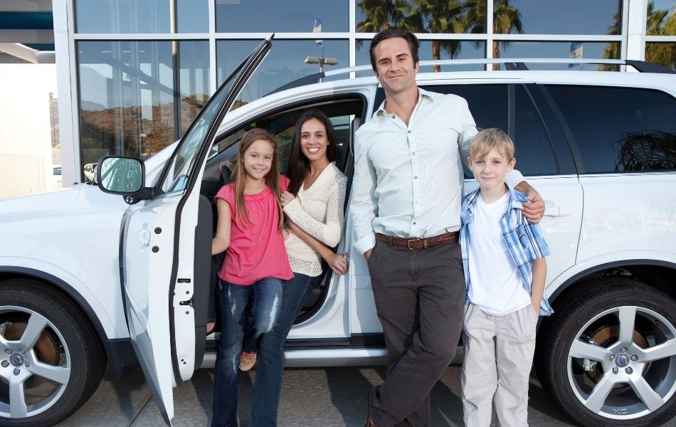 Family in front of a car