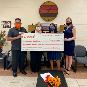 holding a large check at a Volusia County school
