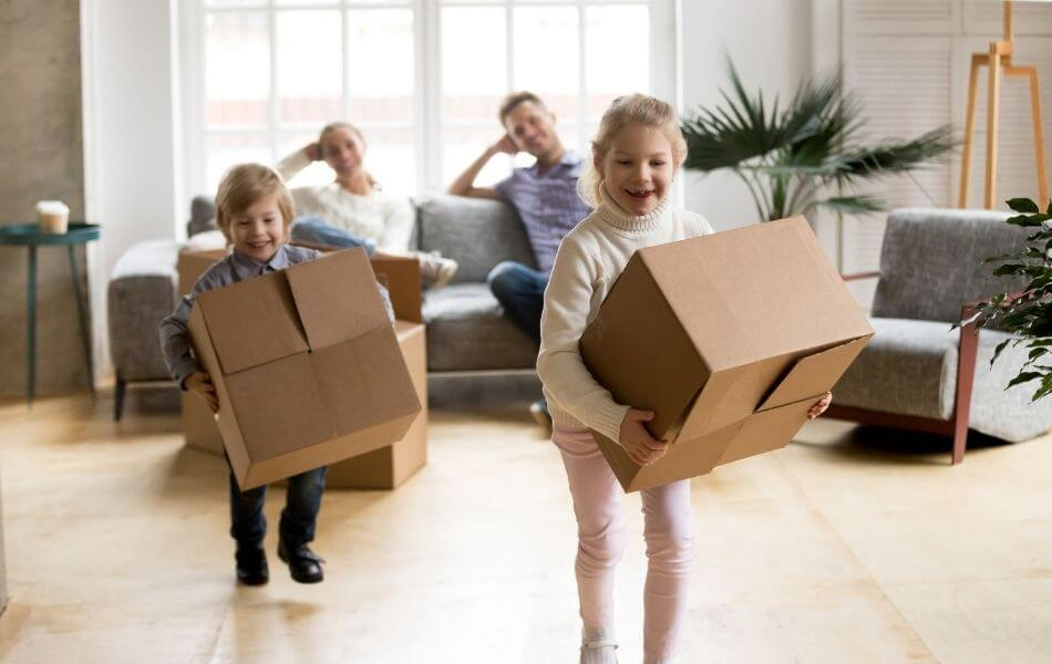 Family in new home. Kids carrying boxes