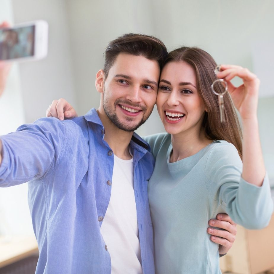 New homeowners taking a selfie with a mobile phone
