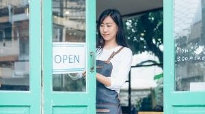 Business Owner Hanging Up 'Open' Sign