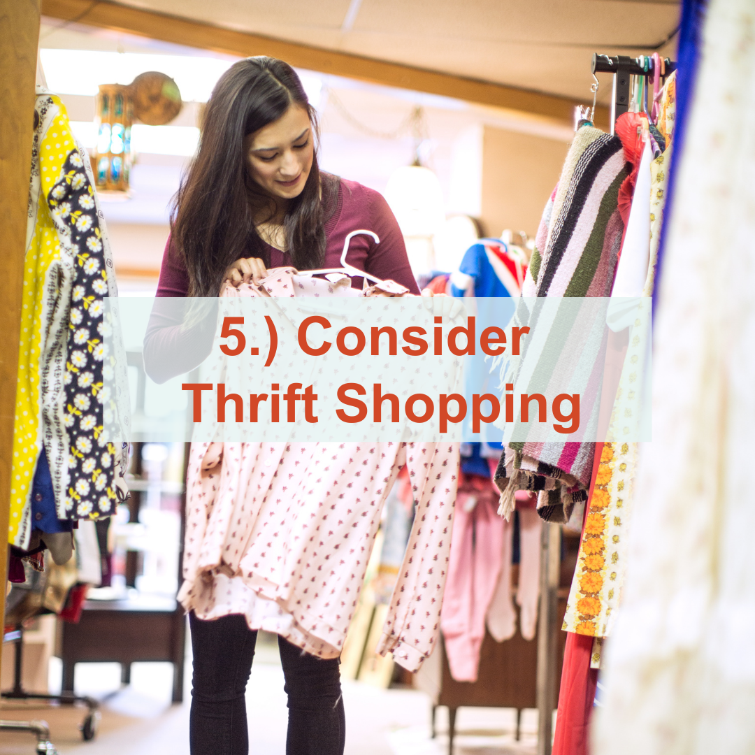 Woman holding a shirt up next to a rack of clothes | Consider Thrift Shopping
