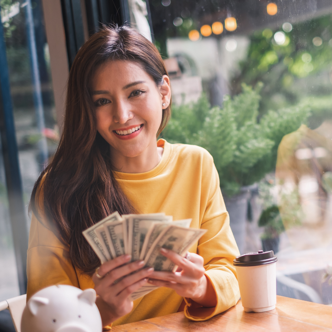 A woman with long brown hair holding a stack of cash sitting at a restaurant table
