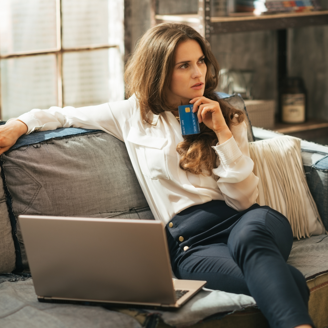 Woman holding a credit card with a laptop in front o her